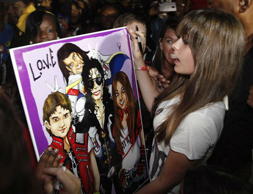 Paris Jackson, daughter of entertainer Michael Jackson, receives a poster of her family from a fan outside Jackson&#39;s boyhood home during a celebration on what would have been Jackson&#39;s  54th birthday, Wednesday, Aug. 29, 2012, in Gary, Ind. &#40;AP Photo&#47;Charles Rex Arbogast&#41; <span class=meta>(AP Photo&#47; Charles Rex Arbogast)</span>