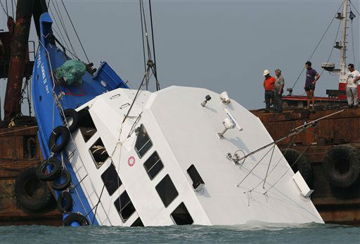 Officials check on a half submerged boat after it collided Monday night near Lamma Island, off the southwestern coast of Hong Kong Island Tuesday Oct. 2, 2012. The boat packed with revelers on a long holiday weekend collided with a ferry and sank off Hong Kong, killing at least 36 people and injuring dozens, authorities said.  &#40;AP Photo&#47;Vincent Yu&#41; <span class=meta>(AP Photo&#47; Vincent Yu)</span>