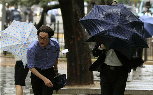 Pedestrians use umbrellas to shield themselves from strong wind and rain caused by Typhoon Bolaven in Seoul, South Korea, Tuesday, Aug. 28, 2012. The powerful typhoon pounded South Korea with strong winds and heavy rain Tuesday, while the nation&#39;s coast guard battled rough seas in a race to rescue fishermen on two Chinese ships that slammed into rocks off the southern coast.  &#40;AP Photo&#47;Lee Jin-man&#41; <span class=meta>(AP Photo&#47; Lee Jin-man)</span>
