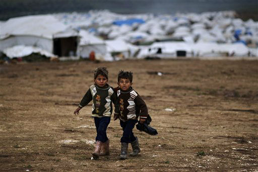 Syrian boys, whose family fled their home in Idlib, walk to their tent, at a camp for displaced Syrians, in the village of Atmeh, Syria, Monday, Dec. 10, 2012. &#40;AP Photo&#47;Muhammed Muheisen&#41; <span class=meta>(AP Photo&#47; Muhammed Muheisen)</span>