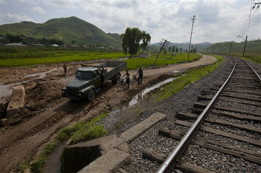 In this Monday, Aug 13, 2012 photo, a North Korean military truck and men on bicycles try to pass through a road, washed out during July 2012 flooding, in Songchon County, North Korea. Twin typhoons are renewing fears of a humanitarian crisis in North Korea, where poor drainage, widespread deforestation and fragile infrastructure can turn even a routine rainstorm into a catastrophic flood. &#40;AP Photo&#47;David Guttenfelder&#41; <span class=meta>(AP Photo&#47; David Guttenfelder)</span>