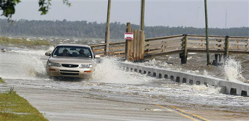 A motorist drives through a flooded street on Tuesday, Aug. 28, 2012, in Bay St. Louis, Miss.  Mandatory evacuation had been ordered by Tuesday in low-lying areas of all three Mississippi coastal counties, and waves were washing across beachside roads as Hurricane Isaac swirled offshore. All three coastal counties also set overnight curfews. The U.S. National Hurricane Center in Miami said Isaac became a Category 1 hurricane Tuesday with winds of 75 mph. It could get stronger by the time it&#39;s expected to reach the swampy coast of southeast Louisiana. &#40;AP Photo&#47;John Bazemore&#41; <span class=meta>(AP Photo&#47; John Bazemore)</span>