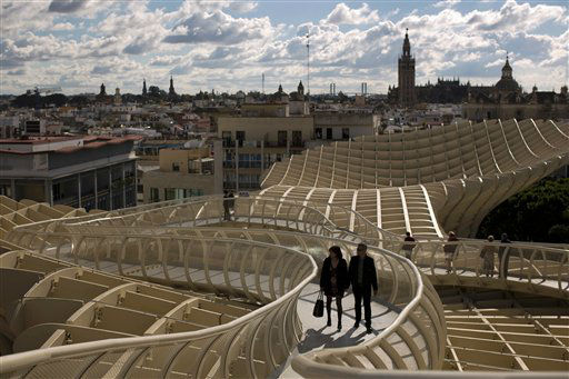 A couple walk along of one the corridors of the Metropol Parasol, overseeing the old city and the Giralda Cathedral of Seville, Spain, Sunday, Nov. 18, 2012. The Metropol Parasol by Jurgen Mayer H. Architects claims to be the world&#39;s largest wooden structure. &#40;AP Photo&#47;Emilio Morenatti&#41; <span class=meta>(AP Photo&#47; Emilio Morenatti)</span>