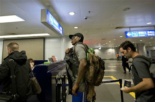Former NBA star Dennis Rodman, center, walks to the check in counter at the departure hall of Beijing Capital International Airport in Beijing Tuesday, Feb. 26, 2013. Rodman, three members of the Harlem Globetrotters basketball team, a VICE correspondent and a production crew from the company are visiting North Korea to shoot footage for a new TV show set to air on HBO in early April, VICE told The Associated Press in an exclusive interview before the group&#39;s departure from Beijing. &#40;AP Photo&#47;Andy Wong&#41; <span class=meta>(AP Photo&#47; Andy Wong)</span>