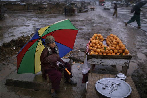 Pakistani boy, Haroun Matiullah, 11, holds an umbrella to shelter himself from rain, while sitting on a roadside hoping to sell his oranges, on the outskirts of Islamabad, Pakistan, Thursday, Thursday, March 14, 2013. Haroun and his family fled Pakistan&#39;s tribal areas in 2009, due to fighting between militants and the army, and took refuge in Islamabad. &#40;AP Photo&#47;Muhammed Muheisen&#41; <span class=meta>(AP Photo&#47; Muhammed Muheisen)</span>