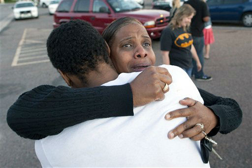Shamecca Davis hugs her son Isaiah Bow, who was an eye witness to the shooting, outside Gateway High School where witness were brought for questioning Friday, July 20, 2012 in Denver.  After leaving the theater Bow went back in to find his girlfriend. &#34; I didn&#39;t want to leave her in there. But she&#39;s ok now,&#34; Bow said.   A gunman wearing a gas mask set off an unknown gas and fired into a crowded movie theater at a midnight opening of the Batman movie &#34;The Dark Knight Rises,&#34; killing at least 12 people and injuring at least 50 others, authorities said. &#40;AP Photo&#47;Barry Gutierrez&#41; <span class=meta>(AP Photo&#47; Barry Gutierrez)</span>