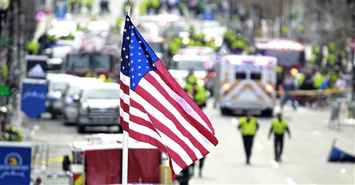 "<div class=""meta image-caption""><div class=""origin-logo origin-image ""><span></span></div><span class=""caption-text"">A flag flies over the finish line as medical workers aid injured people following an explosion at the finish line of the 2013 Boston Marathon in Boston, Monday, April 15, 2013. Two explosions shattered the euphoria at the finish line, sending authorities out on the course to carry off the injured while the stragglers were rerouted away from the smoking site of the blasts. (AP Photo/Charles Krupa) (AP Photo/ Charles Krupa)</span></div>"
