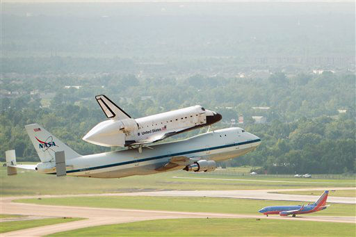 The space shuttle Endeavour, carried atop NASA's 747 Shuttle Carrier Aircraft, passes over neighborhoods near Hobby Airport during a flyover on Wednesday, Sept. 19, 2012, in Houston.