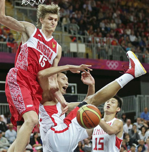 China&#39;s Yi Jianlian, center, kicks his leg up as he drops to the court while battling for a rebound with Russia&#39;s Andrei Kirilenko, left, during a men&#39;s basketball game at the 2012 Summer Olympics, Tuesday, July 31, 2012, in London.  At right is China&#39;s Zhou Peng. &#40;AP Photo&#47;Charles Krupa&#41; <span class=meta>(AP Photo&#47; Charles Krupa)</span>