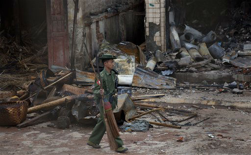An army officer walks with brooms in front of a burned building that housed an orphanage for Muslim children in Lashio, northern Shan State, Myanmar, Thursday, May 30, 2013. Many Buddhists and Muslims stayed locked inside their homes and shops were shuttered after two-days of violence in Lashio town, near the border with China, the latest region to fall prey to the country&#39;s spreading sectarian violence.&#40;AP Photo&#47;Gemunu Amarasinghe&#41; <span class=meta>(AP Photo&#47; Gemunu Amarasinghe)</span>