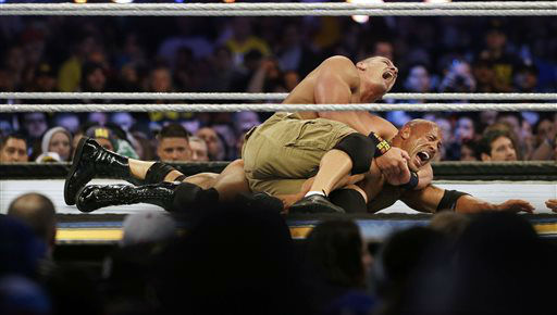Wrestler John Cena, top, chokes Dwayne Douglas Johnson, known as The Rock as they wrestle Sunday, April 7, 2013, in East Rutherford, N.J., during Wrestlemania. &#40;AP Photo&#47;Mel Evans&#41; <span class=meta>(AP Photo&#47; Mel Evans)</span>