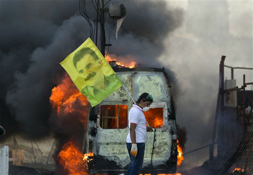 A protester holds  a flag depicting  jailed Kurdish rebel leader Abdullah Ocalan as a van burns during clashes at the Taksim Square in Istanbul Tuesday, June 11, 2013.Hundreds of riot police overran improvised barricades at Istanbul&#39;s Taksim Square on Tuesday, firing tear gas, rubber bullets and water cannons in running battles with protesters who have been occupying the area for more than a week. &#40;AP Photo&#47;Vadim Ghirda&#41; <span class=meta>(AP Photo&#47; Vadim Ghirda)</span>