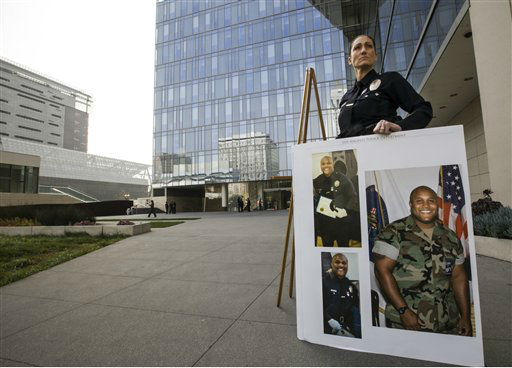 Los Angeles Police Public Information officer Sara Faden holds photos of suspect Christopher Dorner after a news conference at the LAPD headquarters in Los Angeles Thursday, Feb. 7, 2013. Police launched a massive manhunt for a former Los Angeles officer suspected of going on a killing spree, slaying a couple over the weekend, opening fire on two Los Angeles officers early Thursday and then ambushing two other police officers, killing one. At left, Assistant Chief Sandy Jo MacArthur. &#40;AP Photo&#47;Damian Dovarganes&#41; <span class=meta>(AP Photo&#47; Damian Dovarganes)</span>