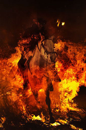 "<div class=""meta ""><span class=""caption-text "">A man rides a horse through a bonfire in San Bartolome de Pinares, Spain, Wednesday, Jan. 16, 2013, in honor of Saint Anthony, the patron saint of animals. On the eve of Saint Anthony's Day, hundreds ride their horses trough the narrow cobblestone streets of the small village of San Bartolome during the ""Luminarias"", a traditional festival that dates back 500 years and is meant to purify the animals with the smoke of the bonfires, and protect them for the year to come. (AP Photo/Daniel Ochoa de Olza) (AP Photo/ Daniel Ochoa De Olza)</span></div>"