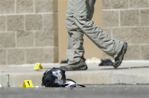 Yellow markers sit next to evidence, including a gas mask, as police investigate the scene outside the Century 16 movie theater east of the Aurora Mall in Aurora, Colo. on Friday, July 20, 2012. A gunman in a gas mask barged into a crowded Denver-area theater during a midnight showing of the Batman movie on Friday, hurled a gas canister and then opened fire in one of the deadliest mass shootings in recent U.S. history. &#40;AP Photo&#47;David Zalubowski&#41; <span class=meta>(AP Photo&#47; David Zalubowski)</span>