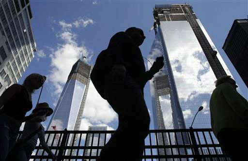 Visitors to the National September 11 Memorial walk below the rising towers 1 World Trade Center, left, and 4 World Trade Center, Monday, Sept. 10, 2012 in New York. Tuesday will mark the eleventh anniversary of the attacks of Sept. 11, 2001. &#40;AP Photo&#47;Mark Lennihan&#41; <span class=meta>(AP Photo&#47; Mark Lennihan)</span>