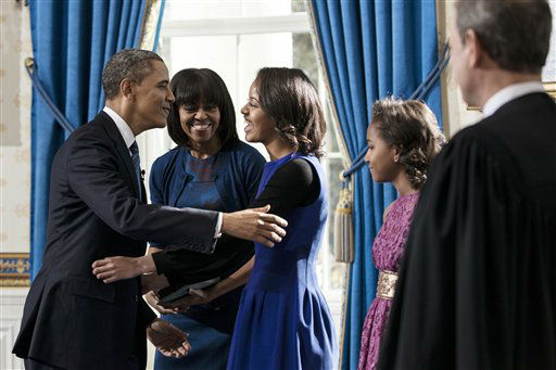 President Barack Obama embraces daughter Malia as first lady Michelle Obama and daughter Sasha, right,  and Supreme Court Chief Justice John Roberts, Jr., look on after the official swearing-in in the Blue Room of the White House, Sunday, January 20, 2013 in Washington.  &#40;AP Photo&#47;Brendan Smialowski, Pool&#41; <span class=meta>(AP Photo&#47; Brendan Smialowski)</span>