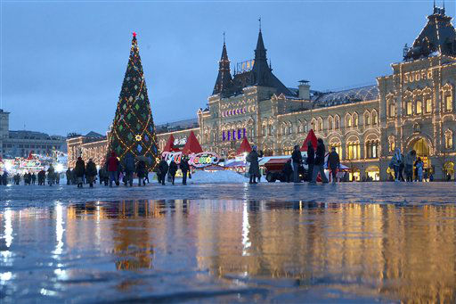 People walk past a Christmas tree in Red Square, with the GUM State Department Store at right, in Moscow, Tuesday, Dec. 4, 2012. A heavy snow fall hit Moscow early morning but it melts in the above-zero temperature. &#40;AP Photo&#47;Alexander Zemlianichenko&#41; <span class=meta>(AP Photo&#47; Alexander Zemlianichenko)</span>