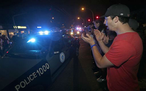 A man applauds as police leave the scene of the arrest of a suspect of the Boston Marathon bombings in Watertown, Mass., Friday, April 19, 2013. Two suspects in the Boston Marathon bombing killed an MIT police officer, injured a transit officer in a firefight and threw explosive devices at police during their getaway attempt. &#40;AP Photo&#47;Charles Krupa&#41; <span class=meta>(AP Photo&#47; Charles Krupa)</span>