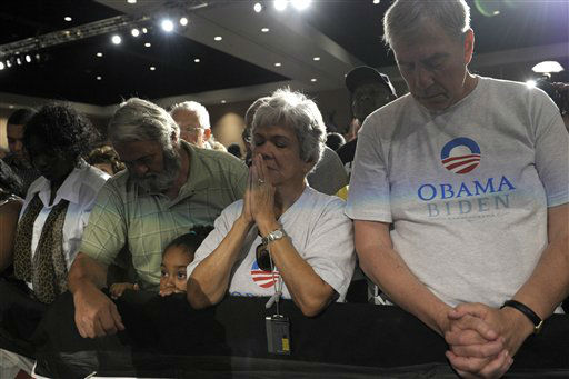 People observe a moment of silence with President Barack Obama for the victims of the Aurora, Colo., shooting at an event at the Harborside Event Center in Ft. Myers, Fla., Friday, July 20, 2012. Obama, who was scheduled to spend the day campaigning in Florida, cancelled his campaign events to return to Washington to monitor the shooting.  &#40;AP Photo&#47;Susan Walsh&#41; <span class=meta>(AP Photo&#47; Susan Walsh)</span>