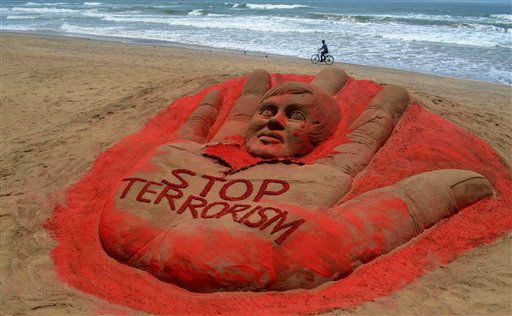 In this Wednesday, April 17, 2013 photo, a cyclist pedals past a sculpture with a message against terrorism, created after attacks in Boston and Bangalore, at the golden sea beach in Puri, India. &#40;AP Photo&#41; <span class=meta>(AP Photo&#47; Uncredited)</span>