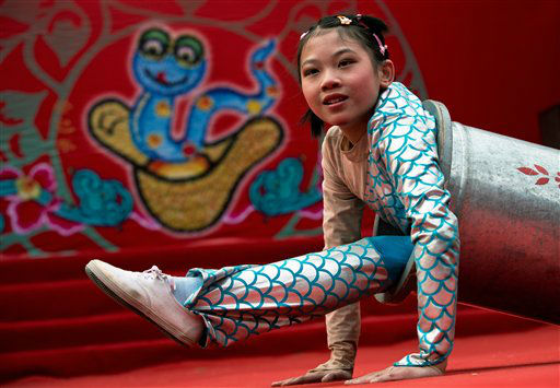 A Chinese girl uses a cylinder while performing an acrobatic show at the Dongyue Temple fair during the second day of the Chinese New Year in Beijing Monday, Feb. 11, 2013. Thousands attended temple fairs across the city to celebrate the arrival of the Year of the Snake. &#40;AP Photo&#47;Andy Wong&#41; <span class=meta>(AP Photo&#47; Andy Wong)</span>