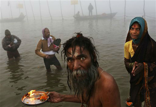 An Indian Hindu holy man performs morning prayers for devotees at Sangam, the confluence of the holy rivers Ganges and Yamuna and mythical Saraswati at the Maha Kumbh Mela in Allahabad, India, Tuesday, Jan. 15, 2013. Millions of Hindu pilgrims are expected to take part in the large religious congregation that lasts more than 50 days on the banks of Sangam during the Maha Kumbh Mela in January 2013, which falls every 12th year. &#40;AP Photo&#47;Kevin Frayer&#41; <span class=meta>(AP Photo&#47; Kevin Frayer)</span>