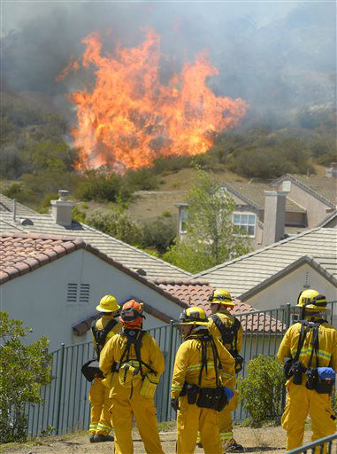 Firefighter looks on as fire burns behind homes during a wildfire that burned several thousand acres, Thursday, May 2, 2013, in Thousand Oaks, Calif.   &#40;AP Photo&#47;Mark J. Terrill&#41; <span class=meta>(AP Photo&#47; Mark J. Terrill)</span>