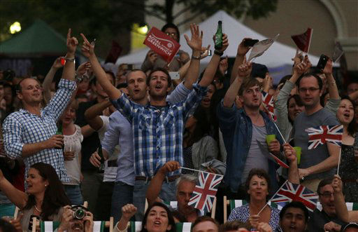 Visitors at a park celebrate during the live telecast of the Opening Ceremony of the 2012 Summer Olympics, Friday, July 27, 2012, in London. &#40;AP Photo&#47;Ng Han Guan&#41; <span class=meta>(AP Photo&#47; Ng Han Guan)</span>