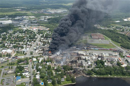 Smoke rises from railway cars that were carrying crude oil after derailing in downtown Lac Megantic, Que., Saturday, July 6, 2013.  A large swath of Lac Megantic was destroyed Saturday after a train carrying crude oil derailed, sparking several explosions and forcing the evacuation of up to 1,000 people. &#40;AP Photo&#47;The Canadian Press, Paul Chiasson&#41; <span class=meta>(AP Photo&#47; Paul Chiasson)</span>
