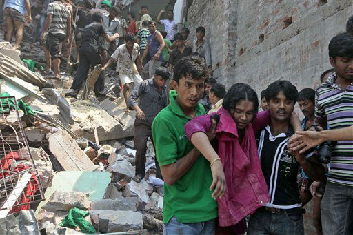 Rescuers assist an injured woman after an eight-story building housing several garment factories collapsed in Savar, near Dhaka, Bangladesh, Wednesday, April 24, 2013. Dozens were killed and many more are feared trapped in the rubble. &#40;AP Photo&#47; A.M. Ahad&#41; <span class=meta>(AP Photo&#47; A.M. Ahad)</span>
