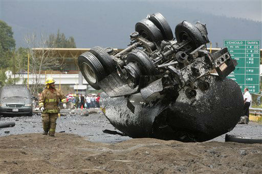A firefighter stands next a flipped over truck that was carrying tar on a highway just west of the state capital city of Morelia, Mexico, Thursday, June 13, 2013. Authorities say the tanker truck carrying tar slammed into a highway toll booth that had temporarily been taken over by protesting teachers. They say seven people are dead and another 14 injured. Most of the dead and injured are believed to be teachers who have been holding a series of protests in the western state of Michoacan. The teachers are protesting educational reforms that would reduce union power in hiring decisions and establish teacher evaluations. (AP Photo/Gustavo Aguado)