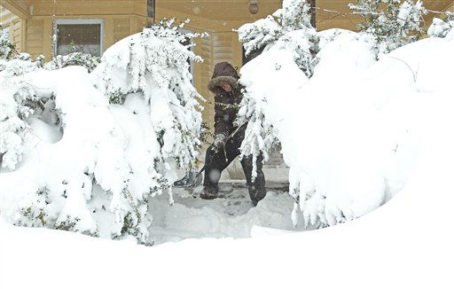 Frank Perry shovels snow from his front porch as the weight of the snow causes the bushes to sag, Saturday, Feb. 9, 2013, in Providence, R.I. A howling storm across the Northeast left the New York-to-Boston corridor shrouded in 1 to 3 feet of snow Saturday, stranding motorists on highways overnight and piling up drifts so high that some homeowners couldn&#39;t get their doors open. More than 650,000 homes and businesses were left without electricity.  &#40;AP Photo&#47;Stew Milne&#41; <span class=meta>(AP Photo&#47; Stew Milne)</span>