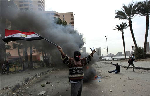 "<div class=""meta ""><span class=""caption-text "">A protester hold the Egyptian national flag during clashes with riot police near Tahrir Square, Cairo, Egypt, Monday, Jan. 28, 2013. Health and security officials say a protester has been killed in clashes between rock-throwing demonstrators and police near Tahrir Square in central Cairo. The officials say the protester died Monday on the way to the hospital after being shot. (AP Photo/Khalil Hamra) (AP Photo/ Khalil Hamra)</span></div>"