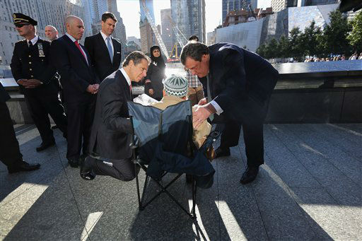 New York Governor Andrew Cuomo, kneeling left, and New Jersey Governor Chris Christie, right, speak with Miah Afsaruddin at ceremonies for the eleventh anniversary of the attacks at the World Trade Center, in New York,Tuesday Sept. 11, 2012. Afsaruddin, from Bangladesh, lost his son Nural Miah and daughter-in-law Shakila Yasmin in the 9&#47;11 attacks. &#40;AP Photo&#47;John Moore,Getty Images, POOL&#41; <span class=meta>(AP Photo&#47; John Moore)</span>