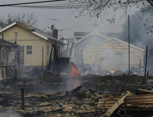 "<div class=""meta ""><span class=""caption-text "">Keith Klein walks through homes damaged by a fire at Breezy Point in the New York City borough of Queens. Tuesday, Oct. 30, 2012. The fire destroyed between 80 and 100 houses Monday night in an area flooded by the superstorm that began sweeping through earlier. (AP Photo/Frank Franklin II) (AP Photo/ Frank Franklin II)</span></div>"