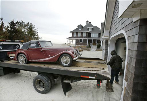 "<div class=""meta image-caption""><div class=""origin-logo origin-image ""><span></span></div><span class=""caption-text"">Adrian Agullar removes a ruined vintage automobile from the garage of a storm-damaged beach front home in Mantoloking, N.J., Friday, Feb. 22, 2013. New Jersey has reached another milestone in its recovery 116 days after Superstorm Sandy struck. One of the hardest-hit Jersey shore communities, Mantoloking, will allow its residents to begin moving back home Friday. It is the last shore town to do so. (AP Photo/Mel Evans) (AP Photo/ Mel Evans)</span></div>"