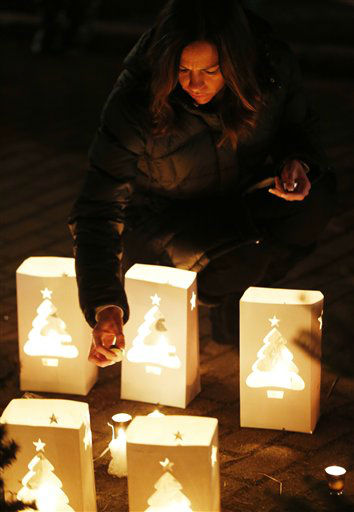 Tracy Tarantino places a candle on a makeshift memorial near the elementary school where a day earlier a gunman opened fire, Saturday, Dec. 15, 2012, in Newtown, Conn. The man, who died from a self-inflicted wound, allegedly killed his mother at their home and then opened fire Friday inside the Sandy Hook Elementary school, massacring 26 people, including 20 children. &#40;AP Photo&#47;Julio Cortez&#41; <span class=meta>(AP Photo&#47; Julio Cortez)</span>