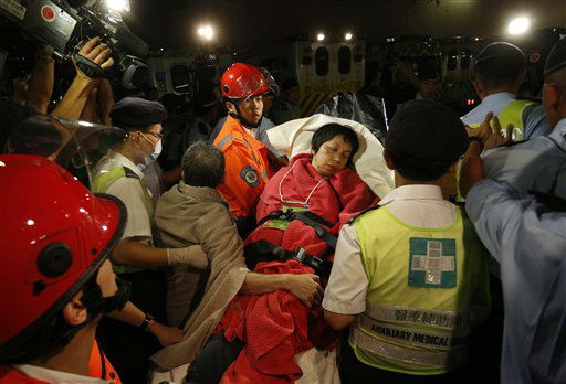 A survivor carried by rescuers, is taken onto shore after a collision involving two vessels in Hong Kong Tuesday, Oct. 2, 2012. Authorities in Hong Kong have rescued 101 people after a ferry collided with a boat and sank. A local broadcaster says eight people died.The government said in a statement that the ferry was carrying about 120 people when the accident happened Monday night near Lamma Island, off the southwestern coast of Hong Kong Island. Few other details were given. &#40;AP Photo&#47;Vincent Yu&#41; <span class=meta>(AP Photo&#47; Vincent Yu)</span>