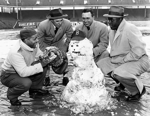 Members of the Brooklyn Dodgers gather around a snowman on the diamond at Ebbets field in the borough of Brooklyn, in New York, April 14, 1950. From left, are Roy Campanella, catcher, Pee Wee Reese, shortshop, Gil Hodges, first baseman, and Jackie Robinson, second baseman. &#40;AP Photo&#47;Anthony Camerano&#41; <span class=meta>(AP Photo&#47; Anthony Camerano)</span>