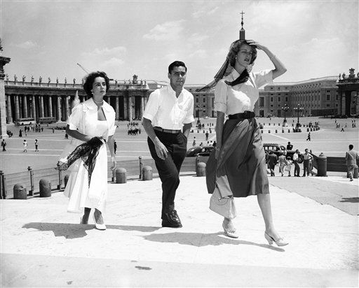"<div class=""meta ""><span class=""caption-text "">British-born movie actress Elizabeth Taylor, who recently married Conrad Hilton Jr., heir to the American hotel chain, is now in Rome pursuing her honeymoon after having stayed a few days in Venice, Aug. 4, 1950.  Left to right are: Taylor, Edward R. Bigelow and Mrs. Bigelow who accompany the honeymooning couple, seen on stairs leading to Saint Peter's Basilica. Elizabeth?s husband. (AP Photo/Walter Attenni) (AP Photo/ Walter Attenni)</span></div>"