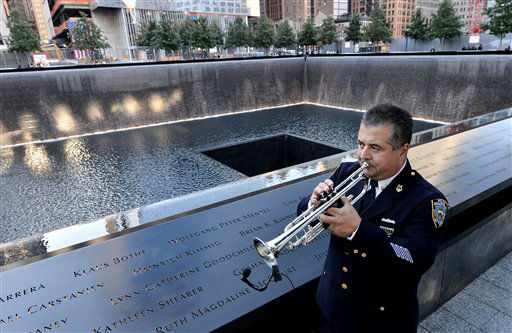 New York City Police Dept. bugler Gabe Perdomo warms up while standing next to the South Pool of the World Trade Center Memorial during the 11th anniversary ceremony to mark the terrorist attacks on the World Trade Center in New York, Tuesday, Sept. 11, 2012. &#40;AP Photo&#47;Justin Lane, Pool&#41; <span class=meta>(AP Photo&#47; Justin Lane)</span>