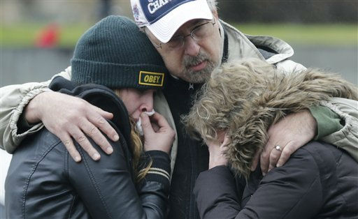 "<div class=""meta ""><span class=""caption-text "">A man clutches two sobbing women at the site of a makeshift memorial for school shooting victims at the village of Sandy Hook in Newtown, Conn., Sunday, Dec. 16, 2012. A gunman opened fire at Sandy Hook Elementary School in the town, killing 26 people, including 20 children before killing himself on Friday. (AP Photo/Charles Krupa) (AP Photo/ Charles Krupa)</span></div>"