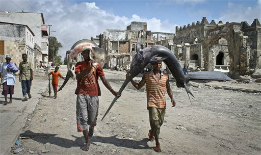Somalis carry a swordfish and a shark on their heads from the ocean to the market in Mogadishu, Somalia, Thursday, Oct. 25, 2012. &#40;AP Photo&#47;Farah Abdi Warsameh&#41; <span class=meta>(AP Photo&#47; Farah Abdi Warsameh)</span>