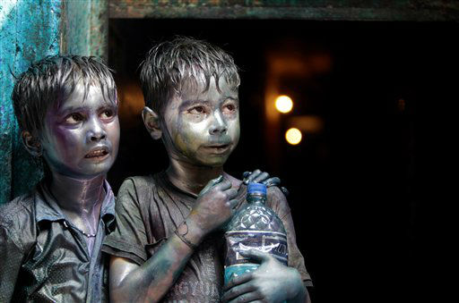 Bangladeshi Hindu children smeared in colors stand at a doorway as they watch Holi festival celebrations in Dhaka, Bangladesh, Thursday, March 28, 2013. Hindus celebrate Holi, the festival of colors, by painting each other in bright pigments, distributing sweets and squirting water at one another. The holiday celebrated mainly in India and Nepal marks the beginning of spring and the triumph of good over evil.   &#40;AP Photo&#47;A.M. Ahad&#41; <span class=meta>(AP Photo&#47; A.M. Ahad)</span>