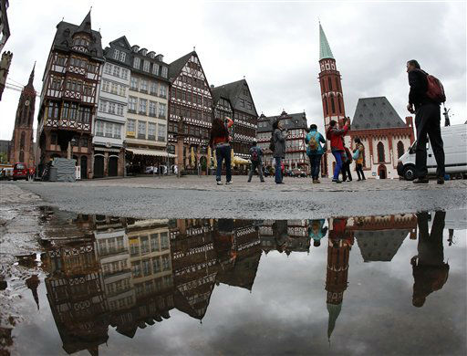In this picture taken with a fisheye lens tourists walk over the Roemerberg square that is reflected in a puddle on a cold and rainy Wednesday in Frankfurt, Germany,  May 22, 2013. &#40;AP Photo&#47;Michael Probst&#41; <span class=meta>(AP Photo&#47; Michael Probst)</span>