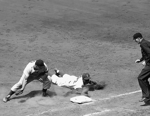 Jackie Robinson, center, Brooklyn Dodger second baseman, scrambles back safely to first base on his stomach in the fourth inning of the first game of twin bill against the Cincinnati Reds at Ebbets Field in the borough of Brooklyn in New York, July 15, 1951. Ted Kluszewski, left, Reds&#39; first baseman, took a throw from catcher Dixie Howell in the pick-off try. &#40;AP Photo&#47;Harry Harris&#41; <span class=meta>(AP Photo&#47; Harry Harris)</span>