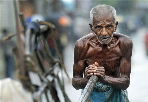 An elderly Sri Lankan laborer pushes a cart as it rains in Colombo, Sri Lanka, Tuesday, Sept. 4, 2012. &#40;AP Photo&#47;Eranga Jayawardena&#41; <span class=meta>(AP Photo&#47; Eranga Jayawardena)</span>