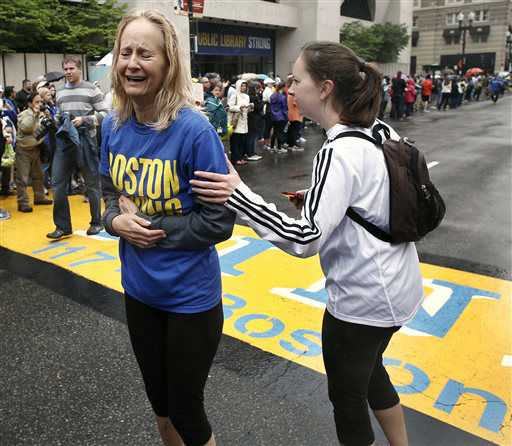 Pam Vingsness, right, comforts her crying mother, Rachel, of Newton, Mass., after they crossed the finish line, as runners who were unable to finish the Boston Marathon on April 15 because of the bombings were allowed to finish the last mile of the race in Boston, Saturday, May 25, 2013. &#40;AP Photo&#47;Winslow Townson&#41; <span class=meta>(AP Photo&#47; Winslow Townson)</span>