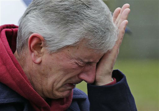 A man reacts at the site of a makeshift memorial for school shooting victims in Newtown, Conn., Sunday, Dec. 16, 2012. A gunman opened fire at Sandy Hook Elementary School in the town, killing 26 people, including 20 children before killing himself on Friday. &#40;AP Photo&#47;Charles Krupa&#41; <span class=meta>(AP Photo&#47; Charles Krupa)</span>